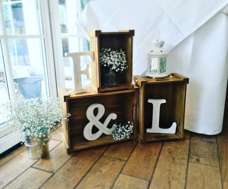 Wood crates used for a simple rustic wedding decoration with the bride and grooms initials, fairy lights and gypsophila
