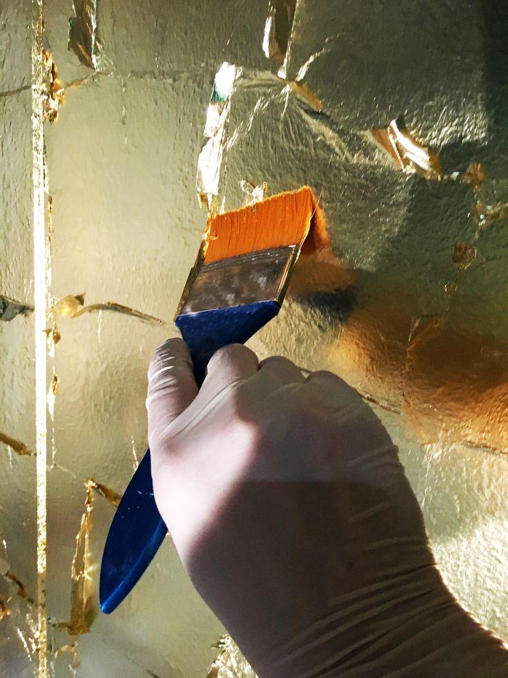 Vergoldungsarbeit mit Blattgold auf einem Messestand. Oberflächengestaltung mit Blattgold oder Schlagmetall. Vergoldung Schlagmetall Messe Ausstellung Goldwand, Wandvergoldung
