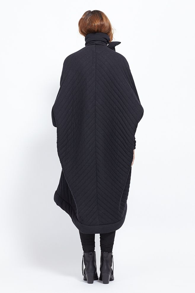 Oversized quilted coat with patchwork throughout. Round neck with draped rib sleeves and concealed snap button closure. Front slit pockets. Fully lined. Slips on. Dry clean.