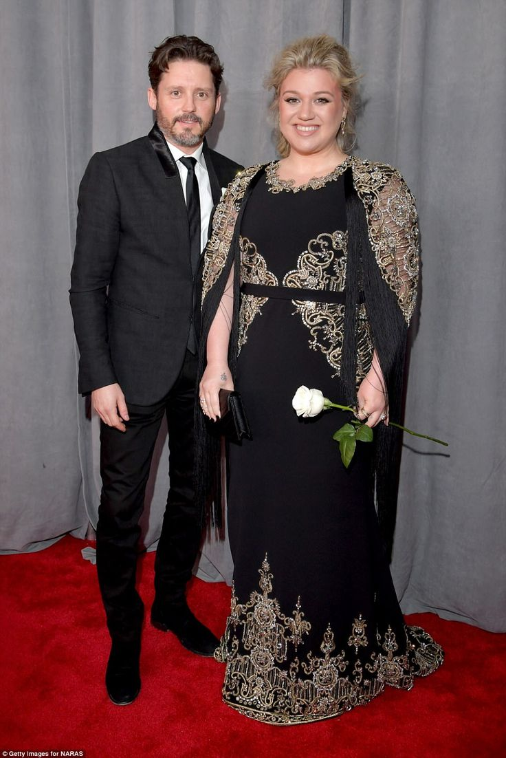 Staying close: Kelly Clarkson wowed in her gold, silver and black detailed frock; she arrived with her husband of four years, Brandon Blackstock