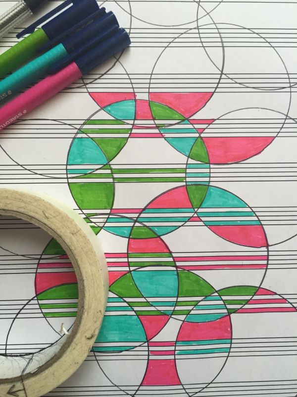 Drawing round a roll of masking tape, making circle pattern doodles on music paper