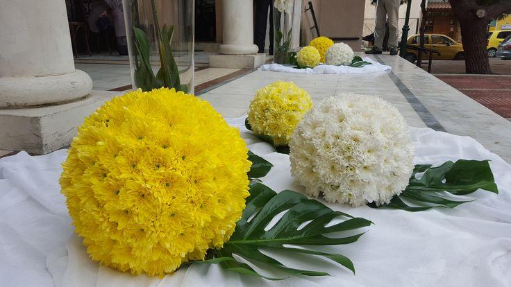 Ο στολισμός εξωτερικά στο γάμο με μπάλες από λουλούδια σε κίτρινα και λευκά χρώματα και φύλλα μονστέρας από κάτω και γάζα λευκή.