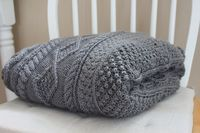 A large grey cable knit blanket made with a free pattern