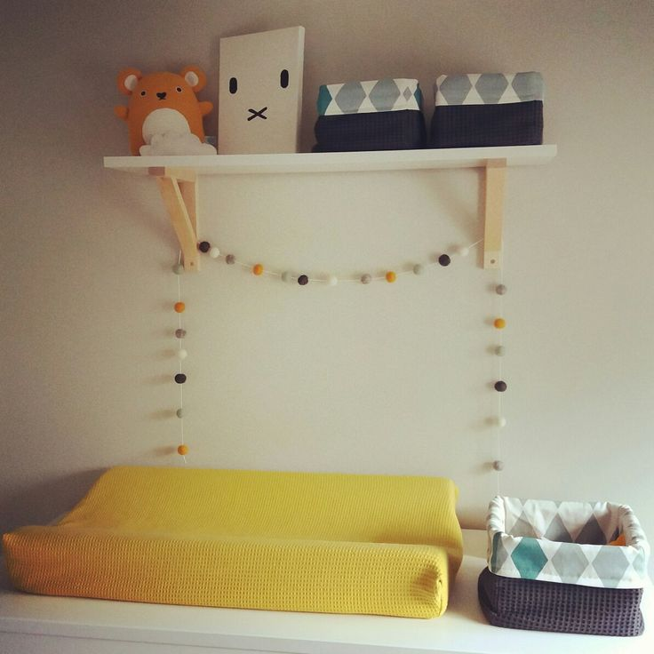 Commode babykamer aangekleed met okergeel en zelfgemaakte mandjes van restjes gordijnstof