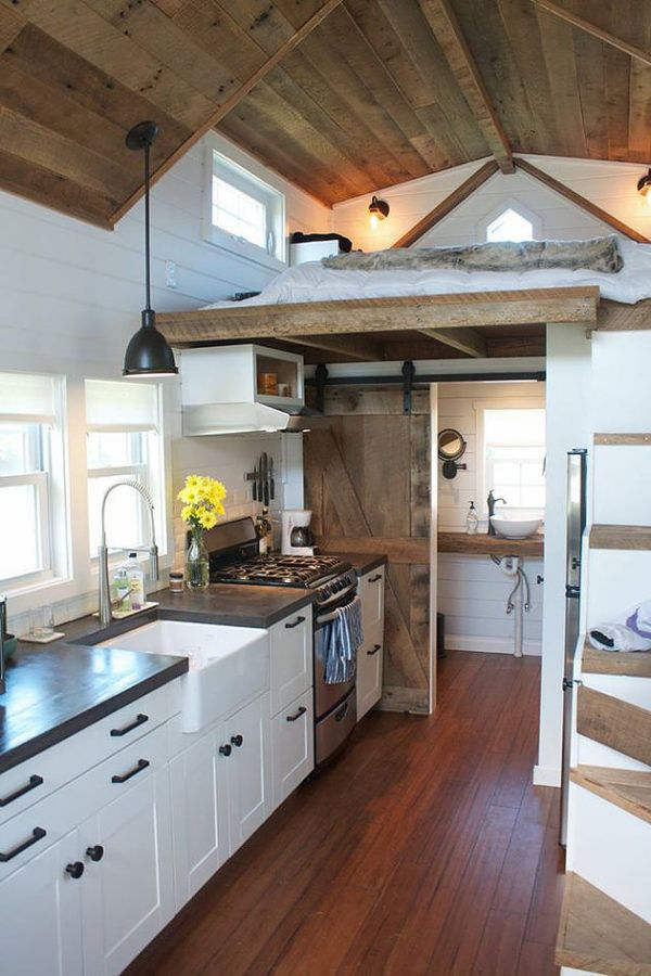 love the wood and white and concrete counters. Beautiful barn door and ceilings.