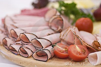A round, wooden board of salami, ham, tomatoes and cheese.    <a href='http://www.dreamstime.com/food-photos-and-table-settings-rcollection4782-resi208938' STYLE='font-size:13px; text-decoration: blink; color:#FF0000'><b>MY FOOD PHOTOS »</b></a>