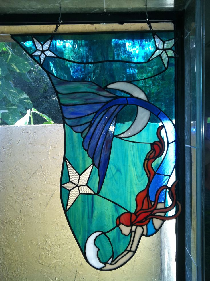 very large blue mermaid stained glass.  i saw a beautiful watercolor featuring a mermaid and decided to use it as inspiration for one of 2 mermaid panels i put in my master bath.  this is the right panel with the blue mermaid.