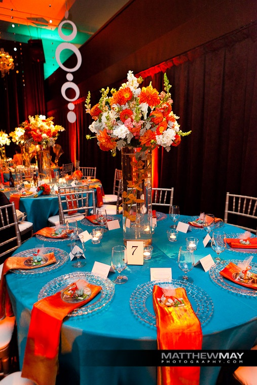 The vibrant orange and white #centerpiece designed by Michael Daigian Design contrasts excellently with the teal linens. #weddings