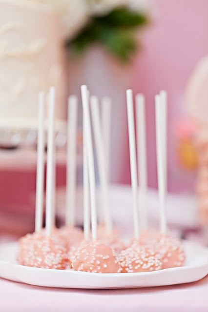 Pink and white sprinkle cake pops featured on pink dessert buffet at wedding reception