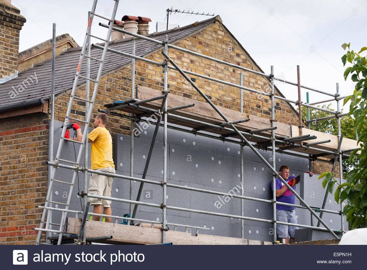 Builders attaching / fitting rigid foam wall insulation sheets Stock Photo, Royalty Free Image: 72414205 - Alamy