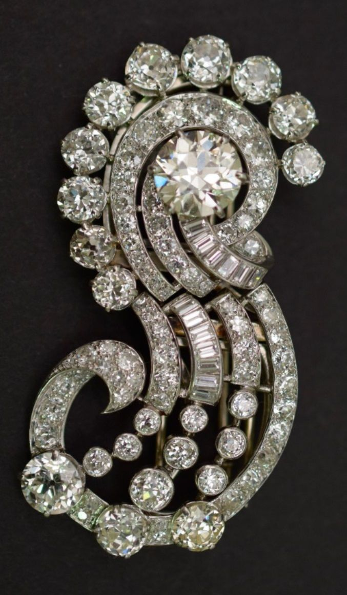 Mauboussin - An Art Deco platinum and diamond double-clip brooch, circa 1935. Designed as a stylised comet, set with old-cut, brilliant-cut and baguette diamonds. The main motif can be mounted on a bracelet. Signed and numbered. 6.2cm. long.