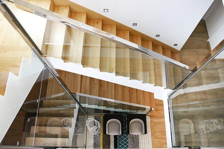 Chiralt Arquitectos I Escalera revestida de parquet (madera) en vivienda moderna con barandilla de cristal.