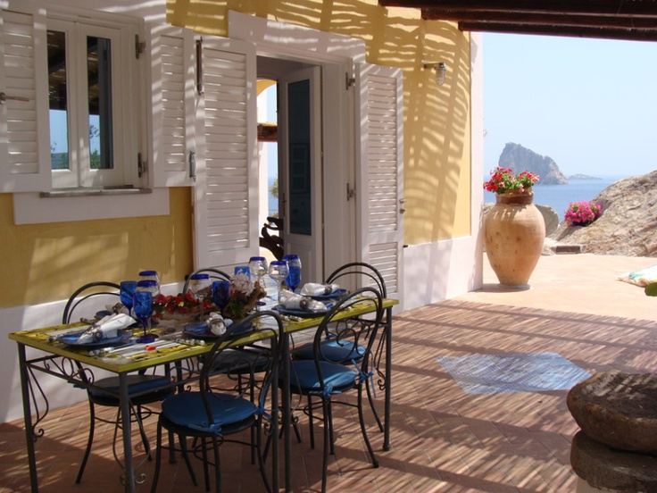 Love the yellow walls, white trim shutters, blue and yellow table set, large pottery and the view! - Eoliana, Sicily Villa in Italy