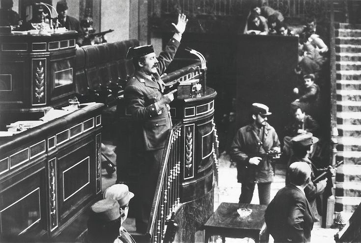 1981 Lt. Col. Antonio Tejero Molina orders everyone to remain seated and be quiet after armed Guardia Civil soldiers stormed the Assembly Hall of the Spanish Parliament. Three hundred deputies and cabinet members were in session to vote upon the succession of premier Suarez. They were released next morning after having been held hostage for almost 18 hours; the coup was a failure. (Manuel Pérez Barriopedro)