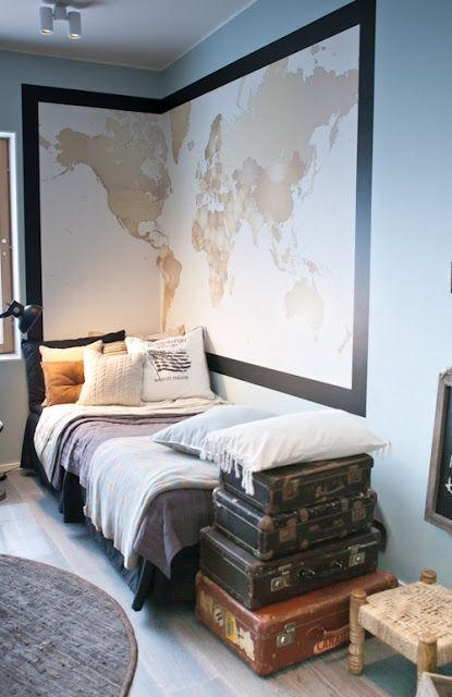 Awesome travel-themed bedroom that would be great for a frequent flier or a guest room! Vintage luggage cases at the foot of the bed, with a large world map wrapped around the wall.