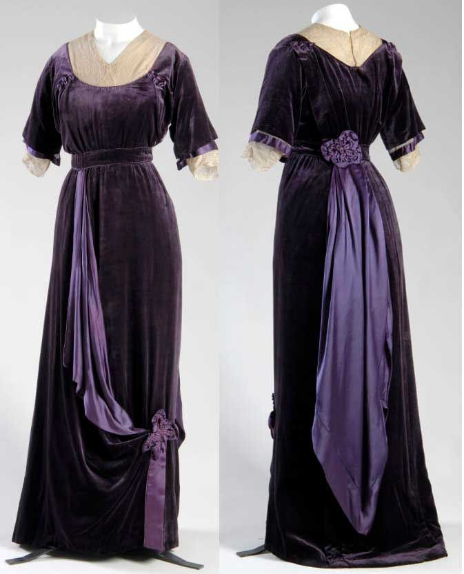 Afternoon dress, 1910, Jeanne Paquin. Small train of purple silk velvet. High stand collar, empire waistline, and elbow-length sleeves. Trimmed with purple silk satin and cream-colored silk lace.