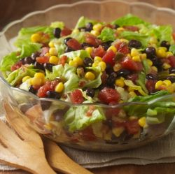 A chopped salad recipe featuring corn, black beans and zesty tomatoes combined with iceberg lettuce for a side salad