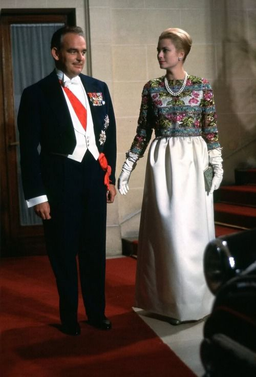 gracefilm:  Prince Rainier and Princess Grace in a white silk sheath dress and intricately embroidered bolero jacket by Balenciaga. Balenciaga often outfitted Princess Grace with suits, dresses, and evening gowns. This one was worn to a gala during an official visit to Paris in October 1959.