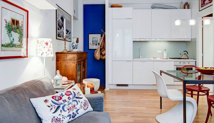 A cozy fresh apartment in central Milan by Nomade Architettura http://www.nomadearchitettura.com/#all  timber flooring, blue wall, white kitchen, panton chair, thonet chair, grey sofa