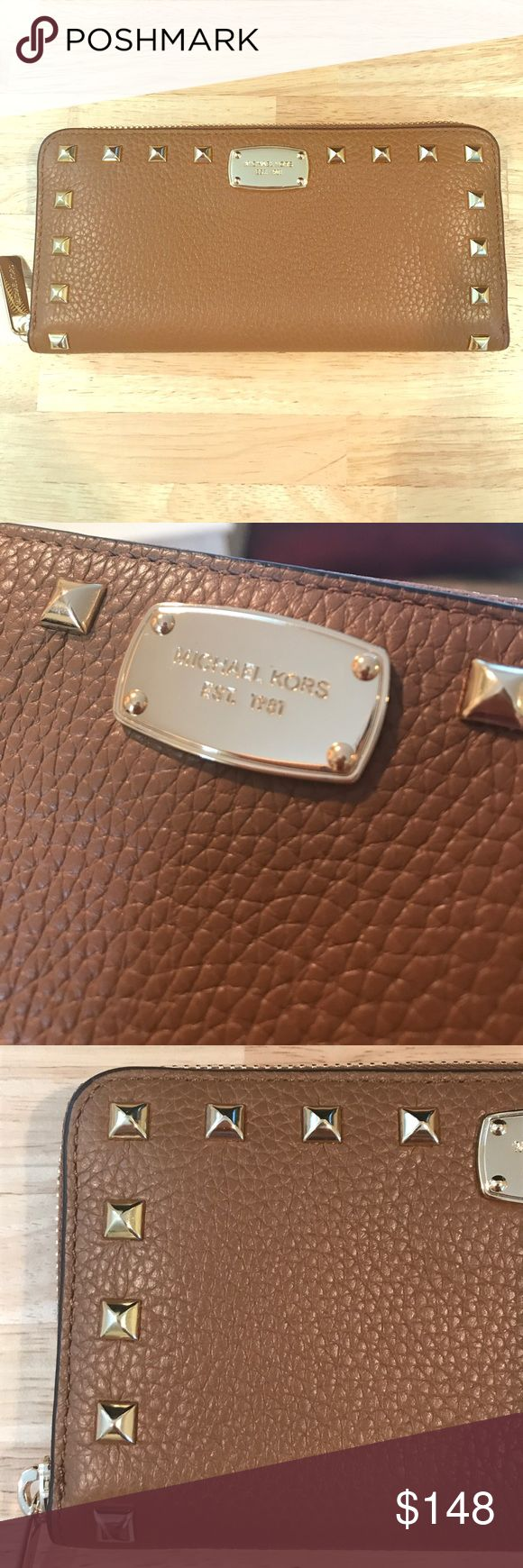 Michael Kors Tan Leather Studded Wallet NWT This Michael Kors wallet is deep tan Leather with gold studs on the perimeter of the front and back. Part of his Jet Set collection and timeless. Inside there are 8 credit card slots, a zippered change purse and 2 cash slots. Gold zipper closure. Retail is $198 Michael Kors Bags Wallets