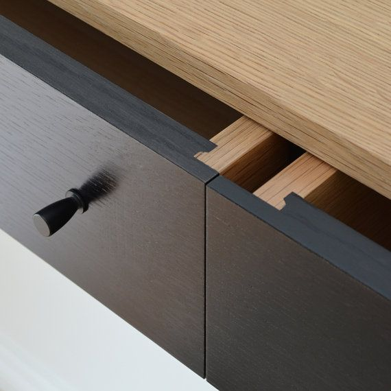 We use solid quarter sawn white oak for the drawers and exterior of our handmade floating console table. The drawer fronts are ebonized with natural