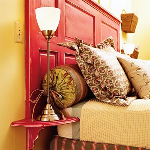 Salvaged door with a perky paint color and useful attached side-tables makes a terrific headboard.