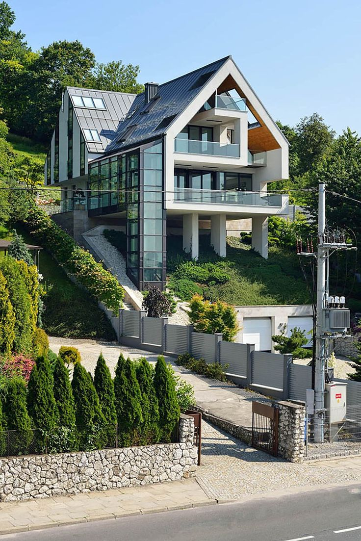 A house on a slope connects to its surroundings through a glass elevator