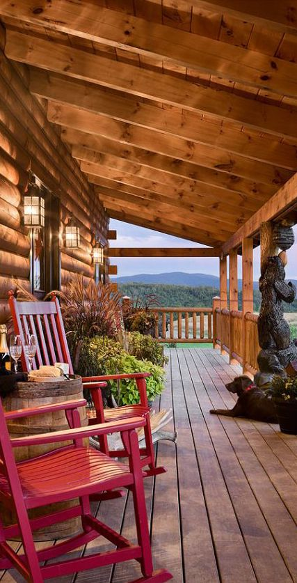 Log home porch - love the bear carving!