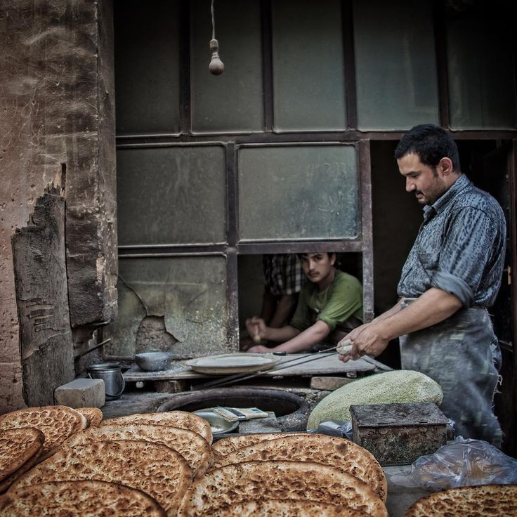 """A baker in Kashgar prepares the local fresh Naan bread (not to be mistaken for the Indian Naan bread, these are quite hard ) in a traditional clay oven."""