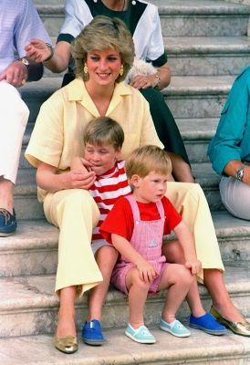 Princess Diana of Wales smiles as she sits with her sons, Princes Harry, front, and William, on the steps of the Royal Palace on the island of Majorca, Spain, Aug. 9, 1987, where the British Royal family is on holiday with the Spanish King Juan Carlos and his family. (AP Photo/John Redman)