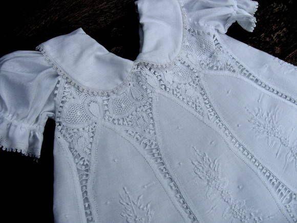 Lindo vestido em cambraia de algodão e renascença branco, com vestido/forro tipo combinação em cambraia 100% algodão.   O vestido de renascença é solto do vestido de cambraia de algodão, que tem a golinha e as mangas, conforme fotos. O fechamento de cada um deles é nas costas, com um botão pequenino. Pode ser usado separadamente.   Medidas do tamanho Pequeno:  Altura total - Do ombro à barra: 40 cm  Largura de ombro à ombro: 18 cm  Largura da frente, na altura da cava: 26 cm (52 cm a largura…