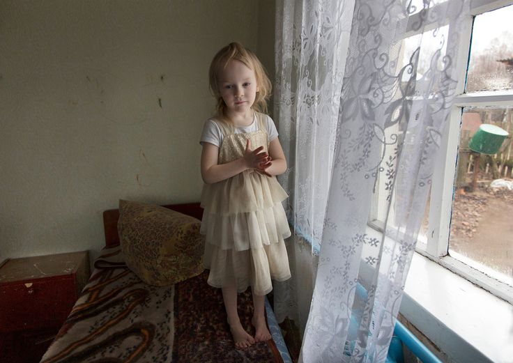 Iana at Home. Iana Vasilieva, 6 years old, at home in the village of Maksimovichi. Iana's father committed suicide a year ago. Many families have seen their desperate situations aggravated by the recent conflicts in the country. © Quintina Valero, Winner, LensCulture Emerging Talent Awards 2016.