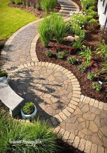 Small circle patio on a curved flagstone path. Love the border stones.