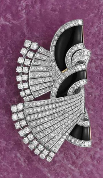 An Art Deco Diamond and Onyx Double Clip Brooch  Designed as a pair of semi-circular onyx plaques with circular-cut diamond borders, extending a graduated series of circular-cut diamond terminals, mounted in platinum, 8 x 4.5 cm.