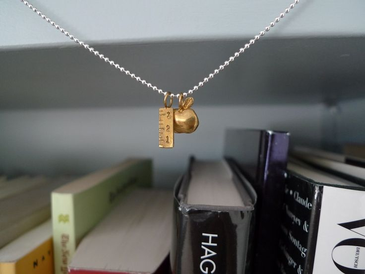 """Teacher """"What I want to be"""" Necklace in Brass and Silver by Slashpile Designs. Teacher ruler and apple charms are hand carved in wax and then cast in brass. They hang on an 18"""" sterling silver ball chain."""