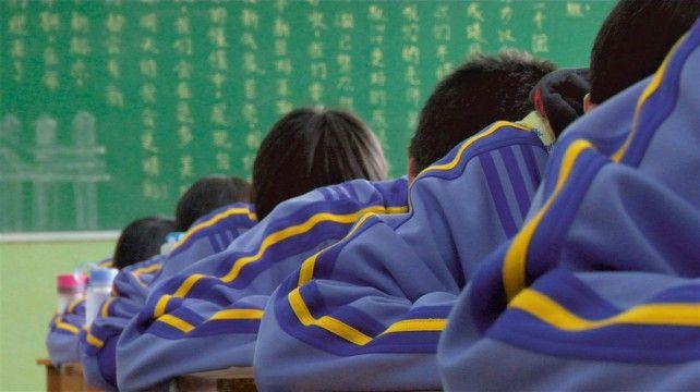 """Bild einer Filmszene aus """"alphabet"""", in der Schüler in Schuluniformen in einer chinesischen Schule sitzen."""