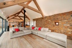 Dieses zeitgenössische Wohnzimmer verfügt über Holz-Deckenbalken und rustikalen nahtlose Grunge Stein Mauer ausgesetzt. Foto von Trewin Design Architekten