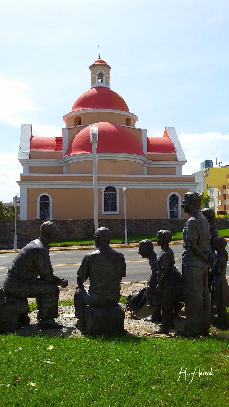 Escultura de Luis Muñoz Marín conversando con el pueblo. Al fondo se puede apreciar la parroquia San Fernando en Carolina Puerto Rico.