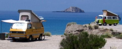 Two generations of Volkswagen camper vans camping it out on a beach in Greece.
