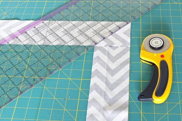 How to DIY a West-Elm Inspired Herringbone Mirror for $7 with a cheap mirror, chevron fabric, wood veneer, and glue.