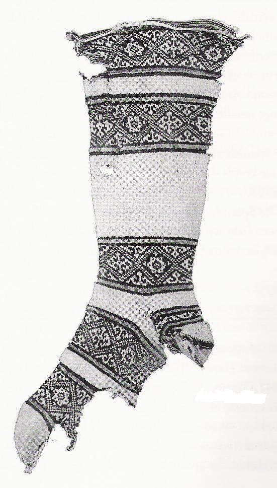 Coptic Socks, 1000 CE, Egypt//    Part of a set of the oldest known pieces of knitting (using sticks as needles and cotton rather than wool).There are quite a few fragments, all of them done in shades of white and indigo, in stockinette. Many of them feature a blessing knitted in Khulfic (decorative Arabic script), symbols intended to ward off evil, or both.