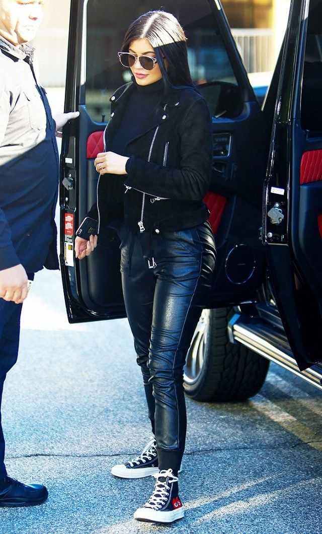 Kylie Jenner wears a turtleneck, suede moto jacket, leather joggers, high-top sneakers, and Dior sunglasses
