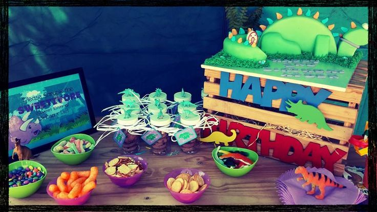 Dinosaur Party.Sweet  and cake table: DIY plastic dino containers with choc chip cookies as party favours. Picture frame with the definition of a sweetavores and sweets and snacks. Wooden crate decorated for the occasion with wooden letters and figures from the location craft shop. I also added some fern leaves and made them peep out the crate. Dinosaur figures  placed around for extra deco.