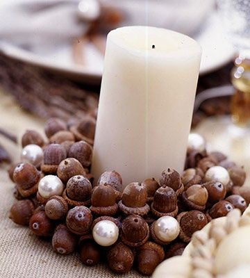 Elegant Candle Display with Acorns and Pearls-  Add a touch of elegance to an autumn element using luminous pearls. Glue acorns to a crafts-foam wreath, placing the caps squarely on its surface. Mix whole acorns and acorn caps for a natural look. Hot-glue large pearl beads to some of the acorn caps to add pops of pearly white to the rich brown ring of nuts. fall-halloween-decor-goodies
