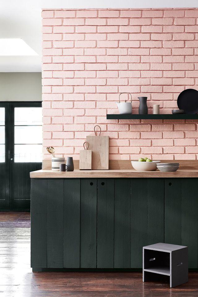 Cuisine rose et noire avec un mur en briques et un petit tabouret