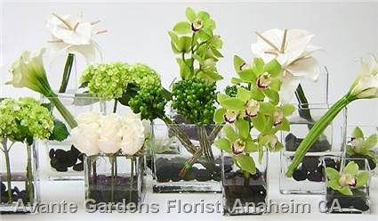 A collection of square vases with river rocks for tablescapes featuring orchids, anthuriums, mini callas, hypericum, hydrangeas and roses in green and white.