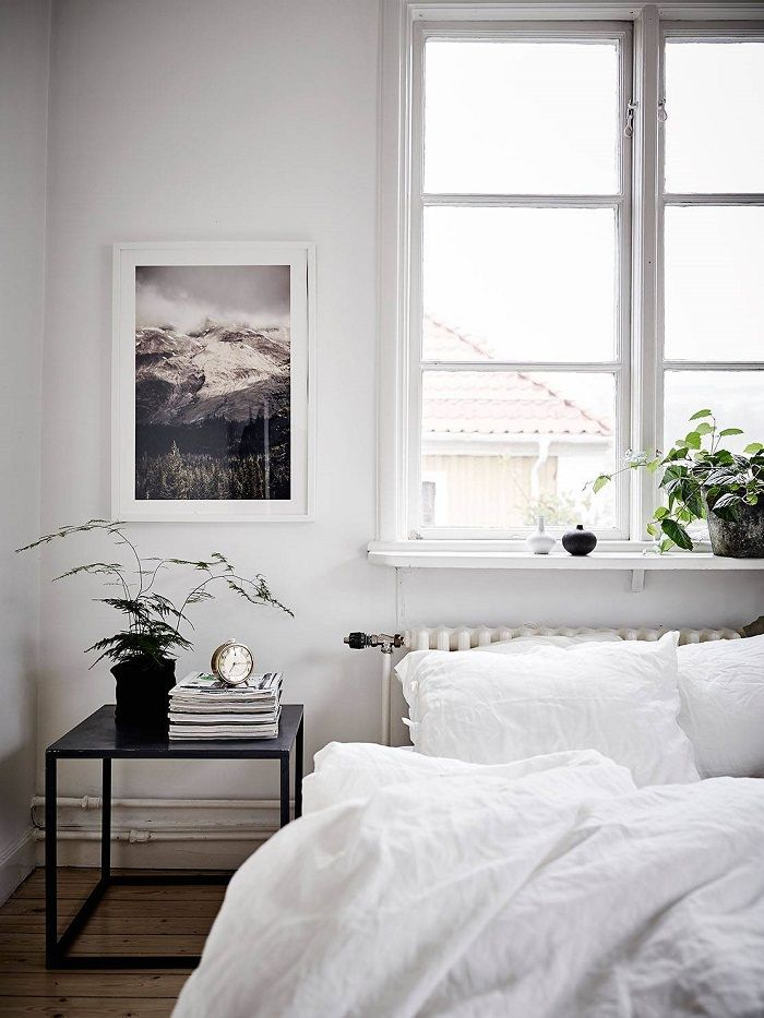 Bedroom with large window above bed, art, simple side table, greenery