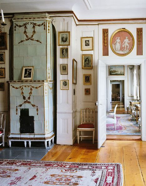 Bedroom at Säbylunds, Narke, Sweden. The gray Gustavian stove has been decorated with yellow and gilded garlands.
