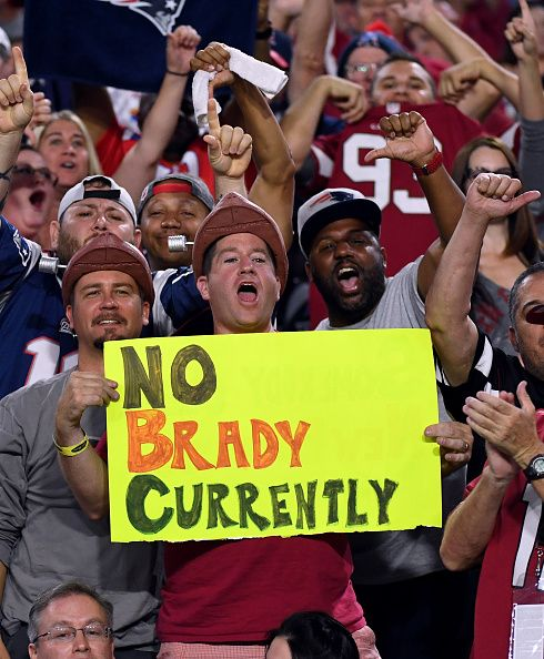Fans of the New England Patriots hold a sign referencing the suspension of…