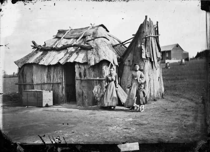 Women and girl in front of their bark cottage on the gold fields, probably near Gulgong, New South Wales. American and Australasian Photographic Company, c1870. State Library of NSW 4 Box 1 No 18117